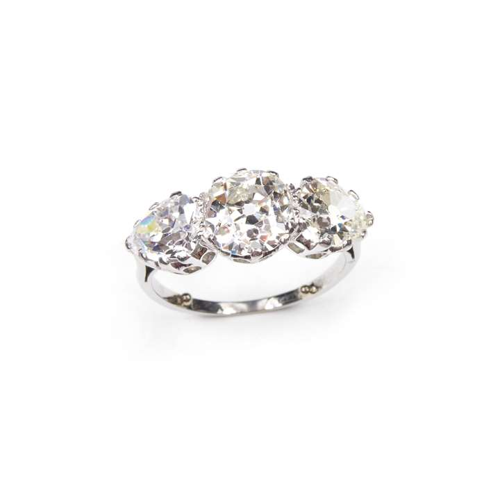 Art Deco three stone diamond ring,  claw set with a central cushion cut diamond between pear shaped diamonds